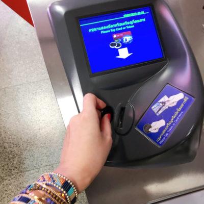 MRTのコイン型の切符を改札に入れるところ